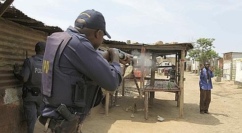 Un police tire sur un manifestant à Diepsloot , en octobre 2009.