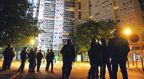 Des policiers en faction devant des immeubles du quartier de La Villeneuve, le 18 juillet à Grenoble, après les violences qui ont suivi la mort d'un braqueur présumé tué par la BAC.