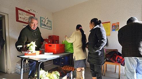 Un bénévole du Secours Catholique (à gauche) distribue des colis de nourriture de la Banque Alimentaire, le 4 décembre 2009 à Saint-Eloy-les-Mines. AFP
