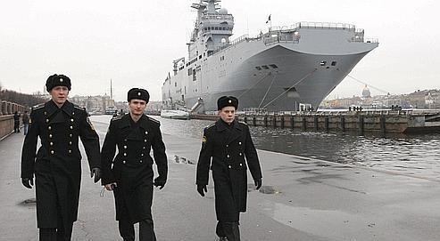 Des marins marchent sur un quai du port de Saint-Petersbourg, où est amarré un porte-hélicoptère Mistral, sur la rivière Neva, le 23 novembre 2009.