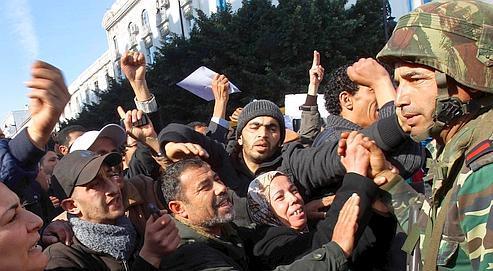 Des manifestants saluent un soldat à Tunis, lundi. L'armée reste très populaire dans le pays.