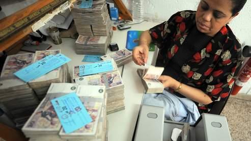 Une employée décompte des billets de banque tunisiens à la Banque centrale.