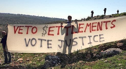 Un Palestinien brandit une bannière, vendredi, lors de la manifestation hebdomadaire de Bilin, qui marque la 6e année de lutte du village contre le mur et l'occupation d'Israël.