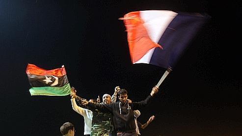 Des Libyens ont brandi leur drapeau national libyen et le drapeau tricolore français après le vote de la résolution onusienne, jeudi soir, dans la ville rebelle de Benghazi.