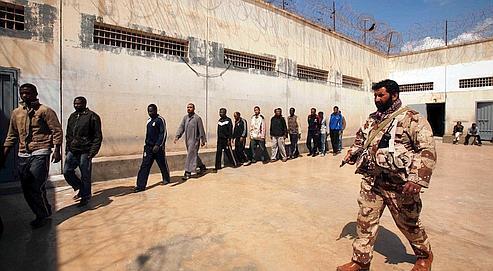 Un insurgé garde des hommes soupçonnés d'être des mercenaires à la solde de Kadhafi dans une prison de Benghazi.