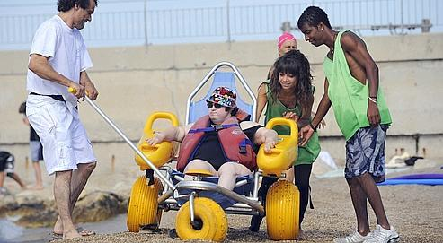 Des jeunes volontaires aident une femme handicapée à prendre un bain de mer, le 29 juillet 2010 sur la plage du Prado à Marseille, dans le cadre de leur service civique. Crédits photo : ANNE-CHRISTINE POUJOULAT/AFP.