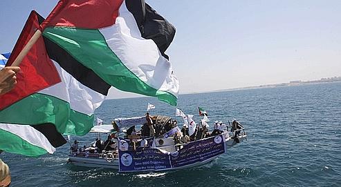 Des Palestiniens attendent l'arrivée d'une flottille d'aide en mai 2010. Cette dernière fut prise d'assaut par les Israéliens, provoquant un tollé international suite à la mort de neuf militants. Crédits photo : HATEM MOUSSA/AP.