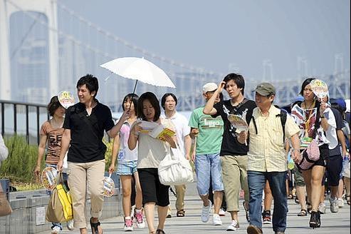 Des passants à Tokyo, le 13 août 2011.