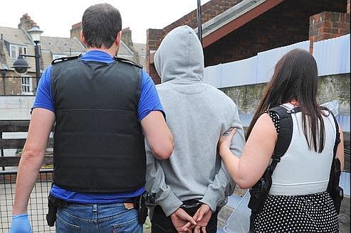 Des officiers de police escortent un jeune arrêté après les émeutes dans le quartier londonien de Brixton.
