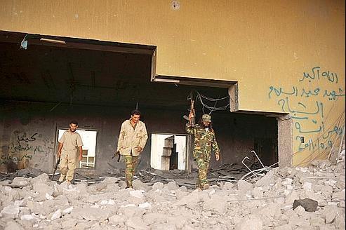 Des soldats du Conseil national de transition, lundi à Syrte, dans les décombres d'une résidence de Kadhafi.