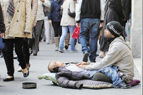 Accompagné d'un enfant lourdement handicapé, un homme fait la manche devant les grands magasins à Paris. (Crédits photo: LE FIGARO)
