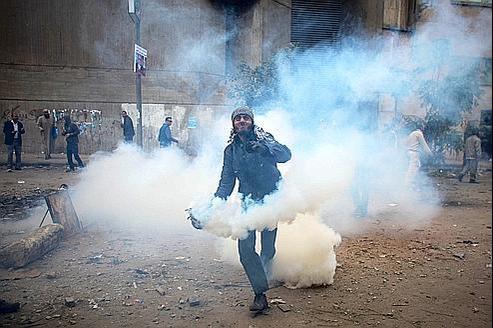Un manifestant renvoie une grenade lacrymogène envoyée par les policiers près du ministère de l'Intérieur dans le centre du Caire, dimanche.