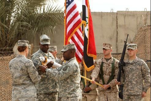 Le général américain Lloyd Austin (deuxième en partant de la gauche) replie jeudi le drapeau de ses forces en Irak.