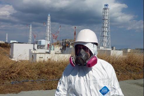 Éric Besson, devant un bâtiment de la centrale nucléaire de Fukushima Daiichi.
