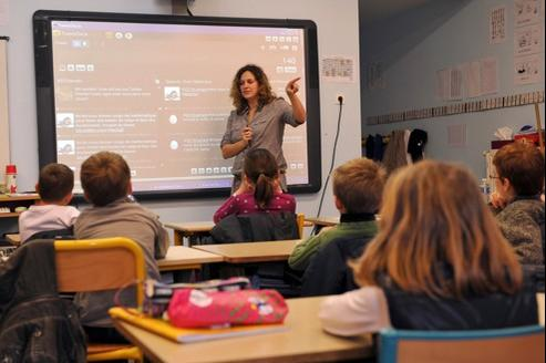 Une institutrice fait cours avec un tableau blanc interactif