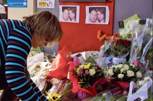 Une femme allume des cierges, dimanche à Montauban, devant le distributeur de billets où les parachutistes français ont été assassinés.