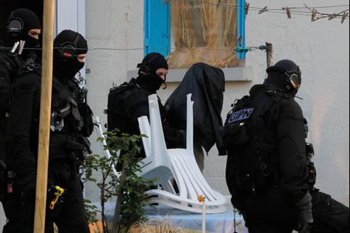 Des policiers des forces spéciales emmènent un suspect, à Couëron, près de Nantes.