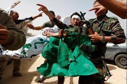 Des révolutionnaires libyens déchirent un drapeau vert, symbole national du pays sous le règne de Kadhafi, découvert à Regdaline après 4 jours de combats entre communautés rivales autour de Zuwara.