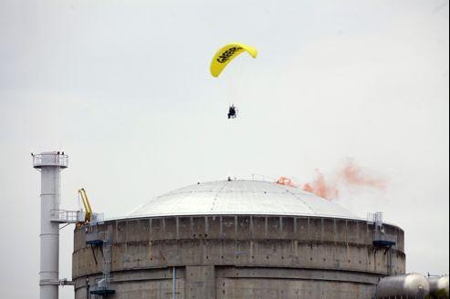 Un militant de Greenpeace lâche un fumigène sur le toit d'un réacteur.