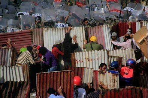 Des manifestants se protègent derrière des tôles ondulées.