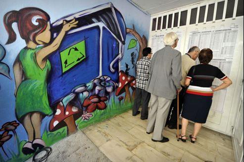 Des électeurs cherchent leurs noms sur les listes d'un bureau de vote, dimanche à Athènes.