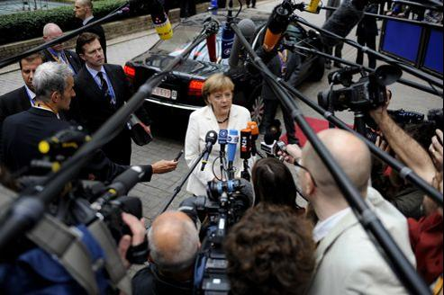 Angela Merkel répond aux journalistes, vendredi, à son arrivée pour le deuxième jour du sommet européen à Bruxelles.