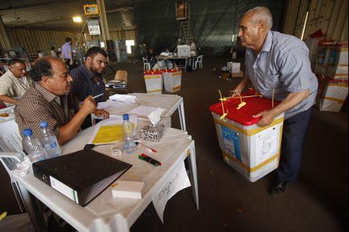 Un membre de la commission électorale porte une urne, dimanche, à Tripoli.