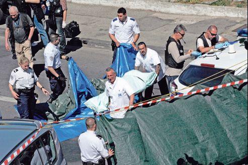 Les services de police font des constatations pendant qu'une victime est évacuée après une fusillade, le 11 mai 2012, dans les quartiers nord de Marseille.