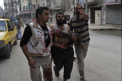 Un homme transporte le corps de son enfant âgé de 5ans, tué au cours des bombardements par les forces gouvernementales syriennes, mardi à Alep.