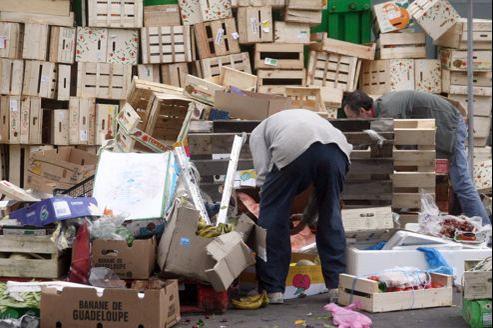 Des personnes récupèrent de la nourriture jetée sur le marché de Belleville.