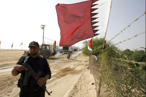 Un membre des forces de sécurité du Hamas près d'un drapeau du Qatar, lundi, à Gaza.