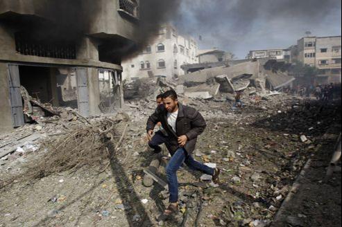 Deux Palestiniens courent dans les rues de Gaza après la destruction d'un immeuble dimanche par des missiles de l'armée israélienne.