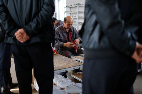 Travailleurs nord-coréens fabriquant des chaussures de football, le 24 octobre, dans la ville chinoise frontière chinoise de Dandong.