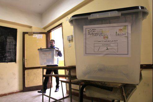 Un employé prépare vendredi au Caire les urnes destinées au référendum, dont le scrutin débute ce samedi.