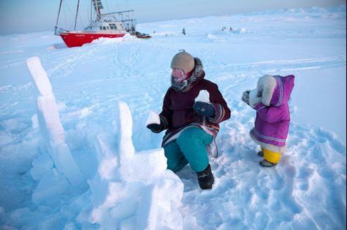 Dans leurs parkas traditionnelles que Lisa, leur amie inuit, leur a offertes, France et Aurore construisent un inuksuk devant leur bateau. Ce cairn de neige, emblème du Nunavut, marque les lieux importants. Artiste, France a fait les beaux-arts de Marseille.