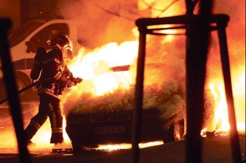 Un pompier éteint une voiture en flammes près de Strasbourg, dans la nuit de lundi à mardi.
