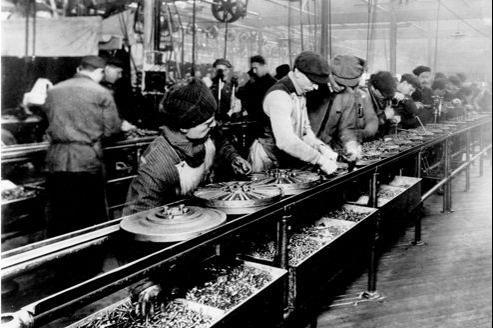Une ligne de production de volants dans l'usine Ford de Highland Park (Michigan, États-Unis), en 1913. L'introduction d'une chaîne de production y a fait chuter le temps nécessaire à la fabrication d'une voiture de 12 heures à 1 h 33.