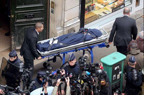 Deux hommes transportent le corps de l'une des militantes kurdes abattues cette nuit à Paris.