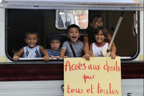 Des enfants roms dans une caravane brandissent une pancarte, à Marseille.