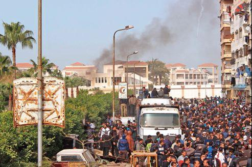 De la fumée s'est élevée après une rafale de coups de feu alors qu'une foule de plusieurs milliers de personnes était rassemblée à Port-Saïd, dimanche.