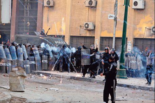 Des policiers à couvert lors d'affrontements avec des manifestants, le 25 janvier, à Alexandrie.