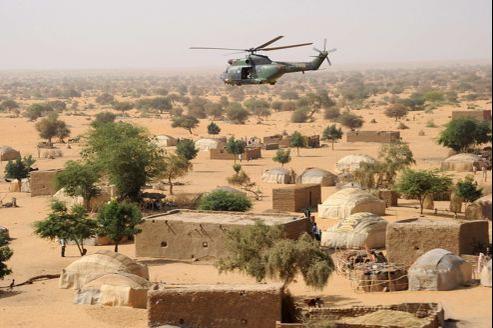Un hélicoptère Puma de l'armée française survole un village malien, le 17 février au nord de Gao.