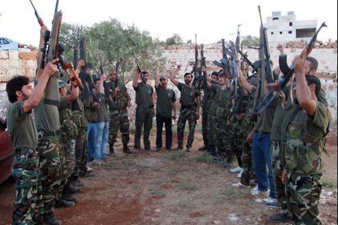 Des combattants de l'Armée syrienne libre brandissent des armes lors d'un entraînement, dans la province d'Idlib.