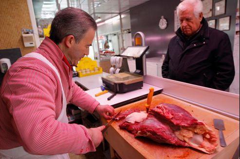 Un boucher prépare de la viande de cheval pour un client à Marseille.