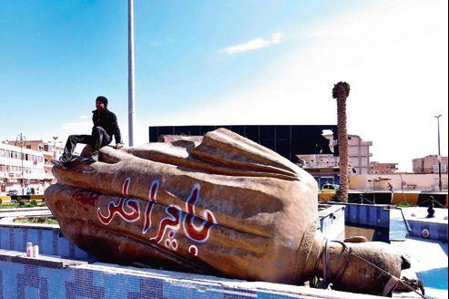 Un Syrien assis sur la statue renversée de l'ancien président Hafez el-Assad à Raqqa, mardi.