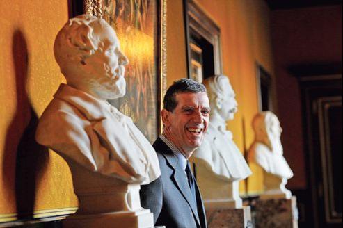 Henri Loyrette pose au mileu des bustes de ses prédecesseurs au Louvre.