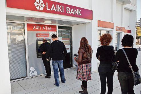 Des Chypriotes font la queue devant un distributeur automatique de la Laiki Bank à Lanarca, samedi, après l'annonce de la taxation des dépôts bancaires dans le cadre du plan de sauvetage de l'île.