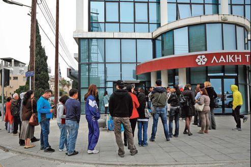 Les Chypriotes continuent à se ruer sur les distributeurs de billets, comme ici devant ceux de la Laiki Bank, la deuxième banque de l'île, jeudi à Limassol.