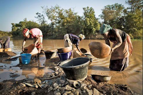 Traditionnellement, ce sont les femmes, courbées en deux, qui lavent le sable aurifère dans les eaux boueuses de la rivière.