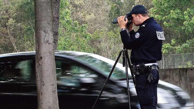 Un policier contrôle la vitesse des véhicules avec un radar mobile.